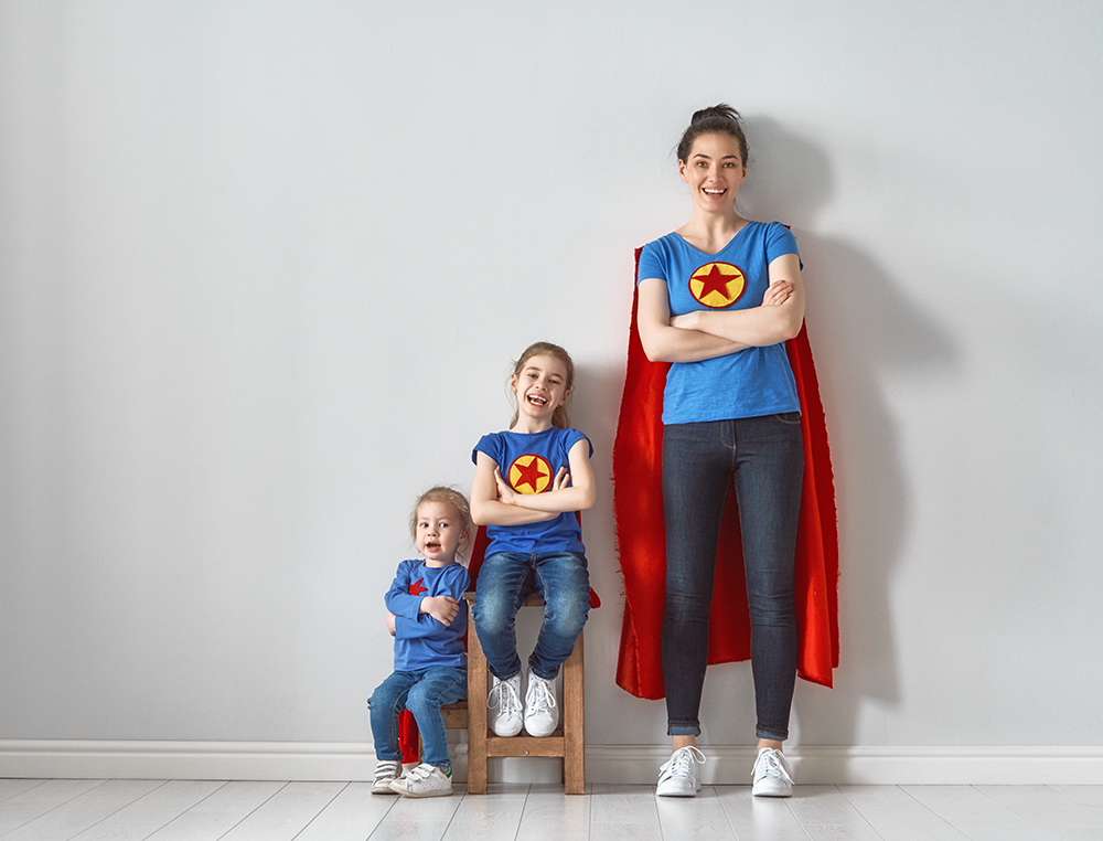 Woman Posting As Superhero With Two Kids Image
