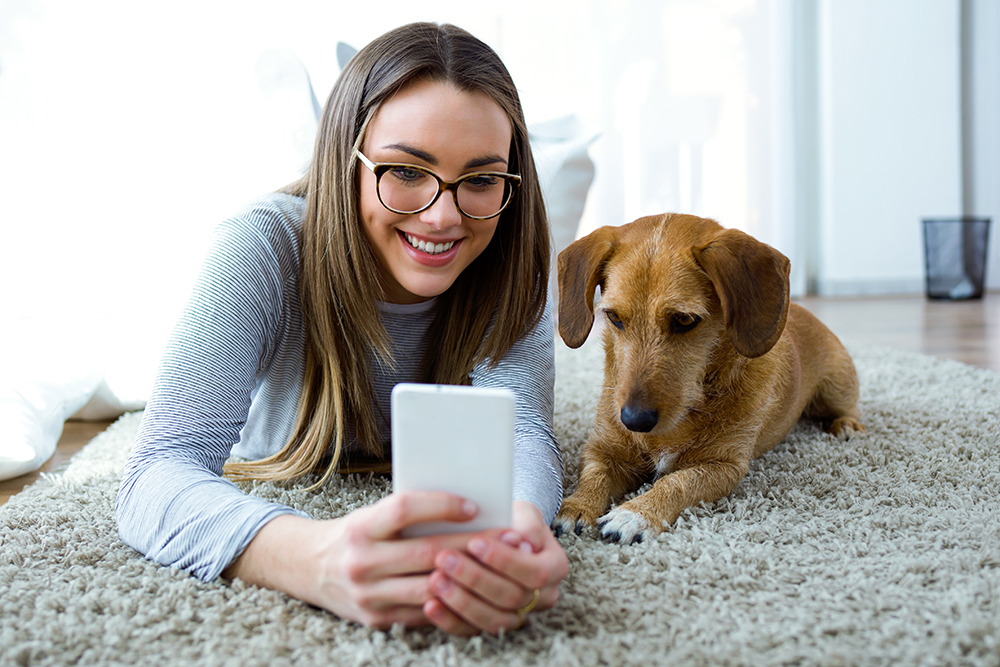 woman smiling with dog on phone image