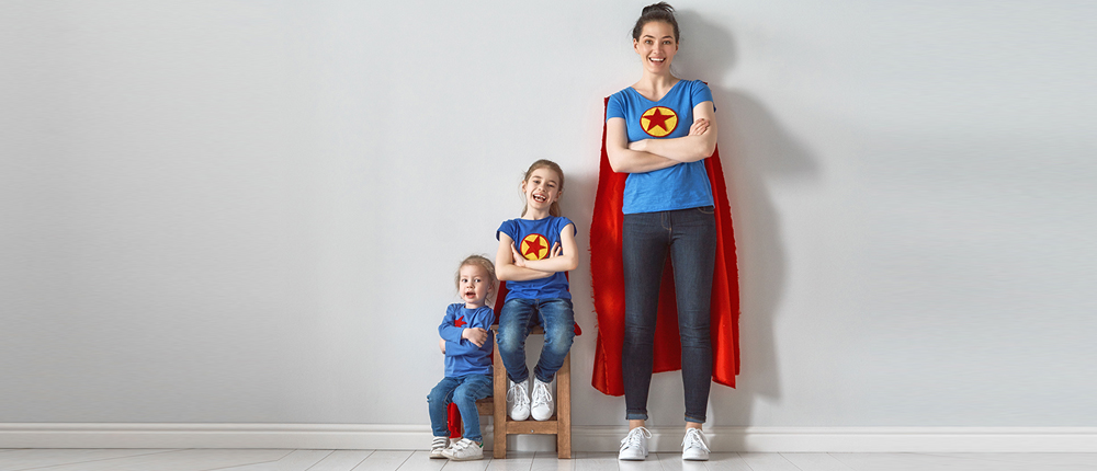 woman posing as superheroes with two little girls image